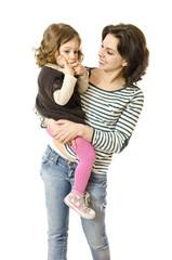 Hija se chupa el dedo y madre sonríe.