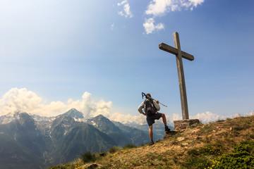 Ragazzo osserva panorama in cima alla vetta con croce
