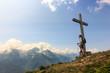 Ragazzo osserva panorama di montagna sotto la croce
