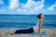 Yang woman practicing yoga by the ocean