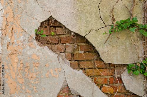mur-z-pekajacym-tynkiem-i-widocznymi-pod-nim-ceglami