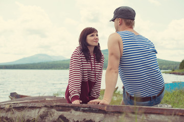 Romantic couple sitting on an old boat and looking at each other