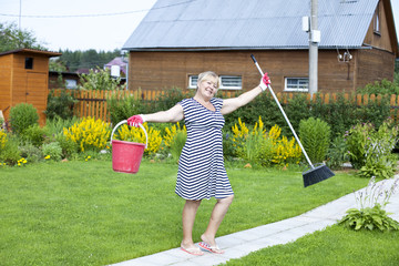Pensioner in the country cottage with a bucket and mop