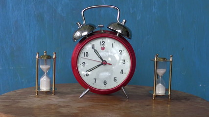 analog alarm-clock and two sand glass, hourglass on table