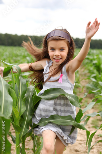Joyful little girl running through the corn field