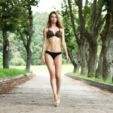 Sexy woman in bikini walking on the summer park