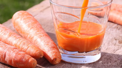 Close-up of glass with pouring carrot juice.