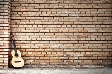 chitarra classica e muro di mattoni