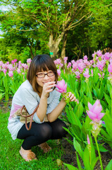 Cute Thai girl sneaking to pickup the pink Siam Tulip.