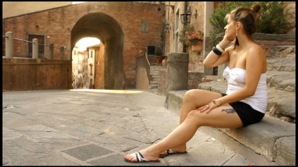 Beautiful woman talking on the phone in vintage italian streets
