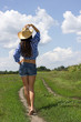 Girl in a checkered shirt on and a cowboy hat in the field