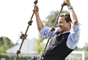 Happy businessman playing, swinging in ropes
