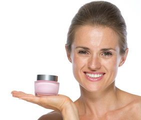 Happy young woman showing cream bottle