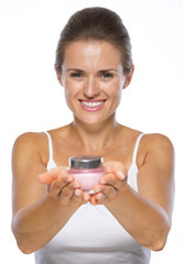Smiling young woman giving cream bottle