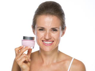 Smiling young woman holding cream bottle