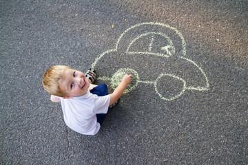 Boy drawing car with chalk