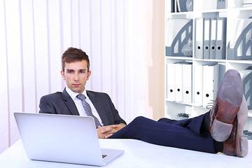 Businessman resting at his office with his shoes on table