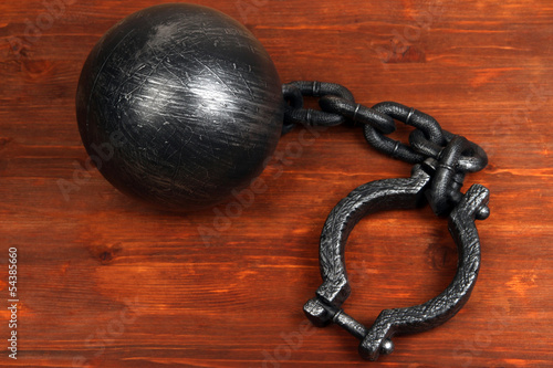 Ball and chain on wooden background