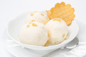 Close-up of ginger ice cream with melted milk and thin waffles