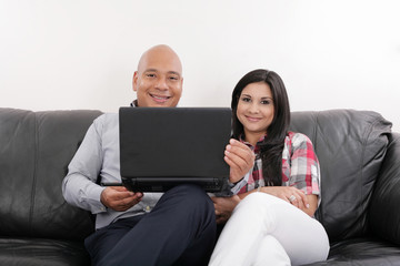 Hispanic Couple on Black Couch with Computer
