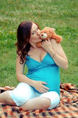 Young woman is wating baby and kissing teddy bear
