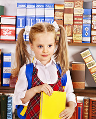 Child with book on bookshelf.