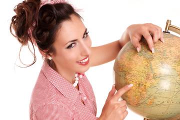 junge Frau zeigt auf einen Globus
