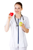 Smiling woman doctor with a green apple and red heart.