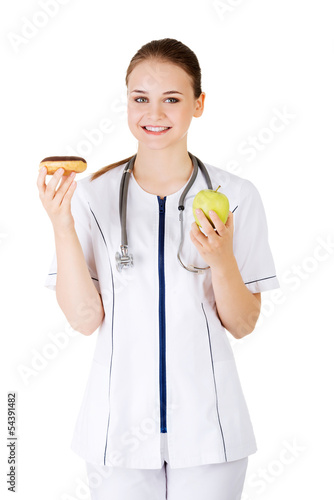 Dietician holding sweet doughnut and fresh healthy green apple.