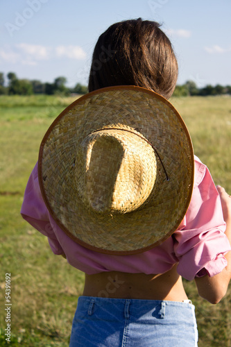 Girl with a cowboy hat in the field