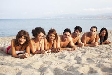 Menschen liegen in einer Linie am Strand