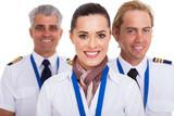 flight attendant standing in front of pilots
