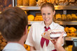 Saleswoman in baker's shop selling bread to customer