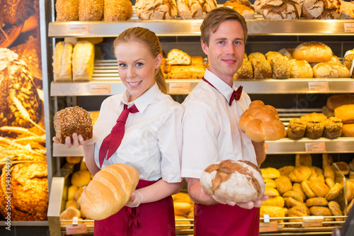 Bakers presenting loafs of bread in a bakery