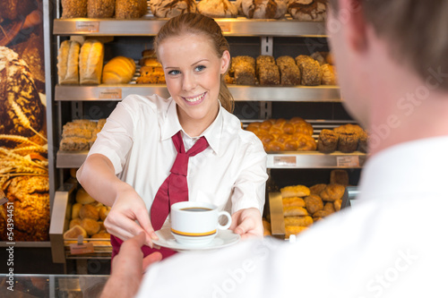 Saleswoman in baker's shop giving cup of coffee to customer