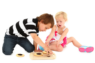 Adorable Caucasian brother and sister sitting on floor with cook
