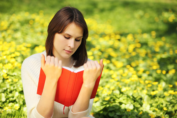 Image of young beautiful woman in summer park reading book