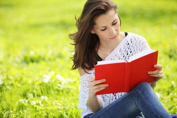 Image of young beautiful woman in summer park reading a book