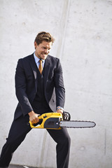 Crazy businessman with a chainsaw