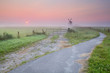 bicycle road to windmill in fog