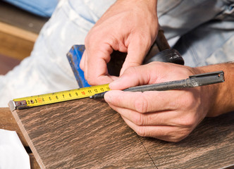 Man measuring a tile piece with a marker