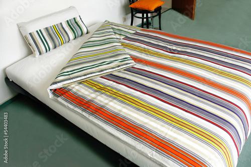Bett mit gestreifter Bettwäsche - 54403483