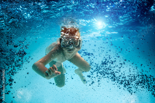 Teenager in the mask and snorkel swim underwater.