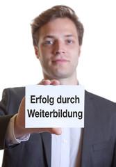 Mann im Anzug mit Karte ERFOLG DURCH WEITERBILDUNG