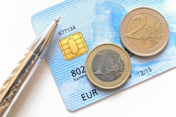 Euro Münzen auf hellblauer Kreditkarte