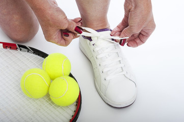 Female tennis player tying shoe lace