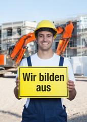 Bauarbeiter mit Schild WIR BILDEN AUS
