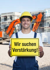 Bauarbeiter mit Schild WIR SUCHEN VERSTÄRKUNG