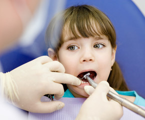 little girl with open mouth during drilling treatment