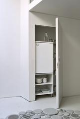 mobile aperto in cucina con oggetti e frigorerifero